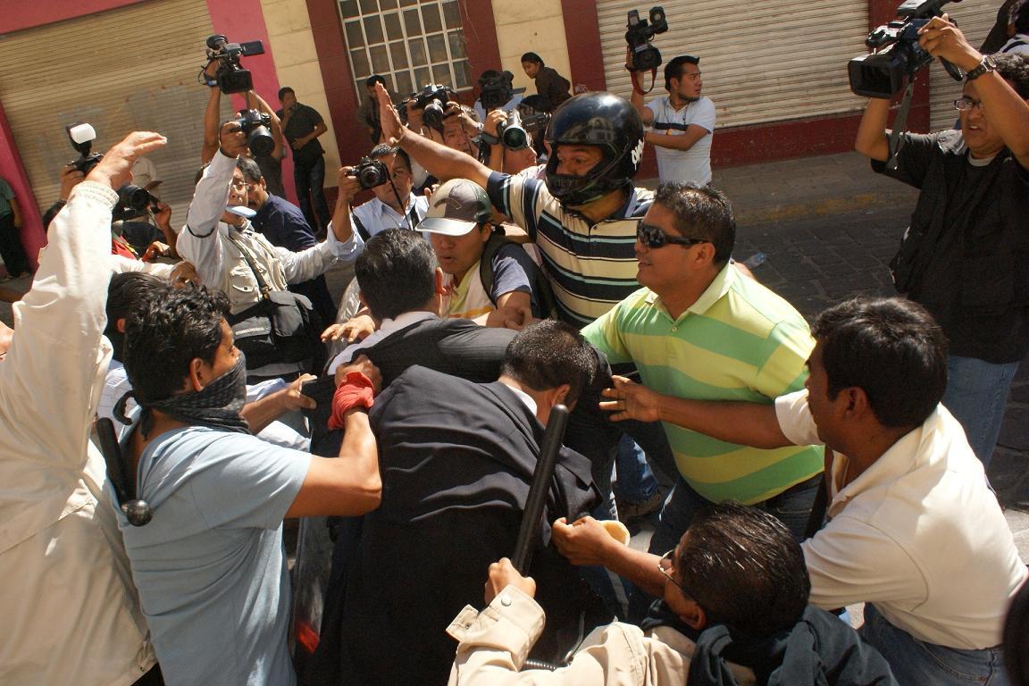 Momento en el que el funcionario comenzó a ser agredido por los docentes.