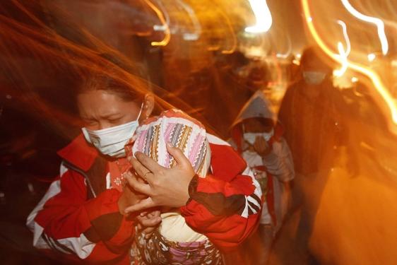 Una madre cubre a su hijo mientras huye del lugar.